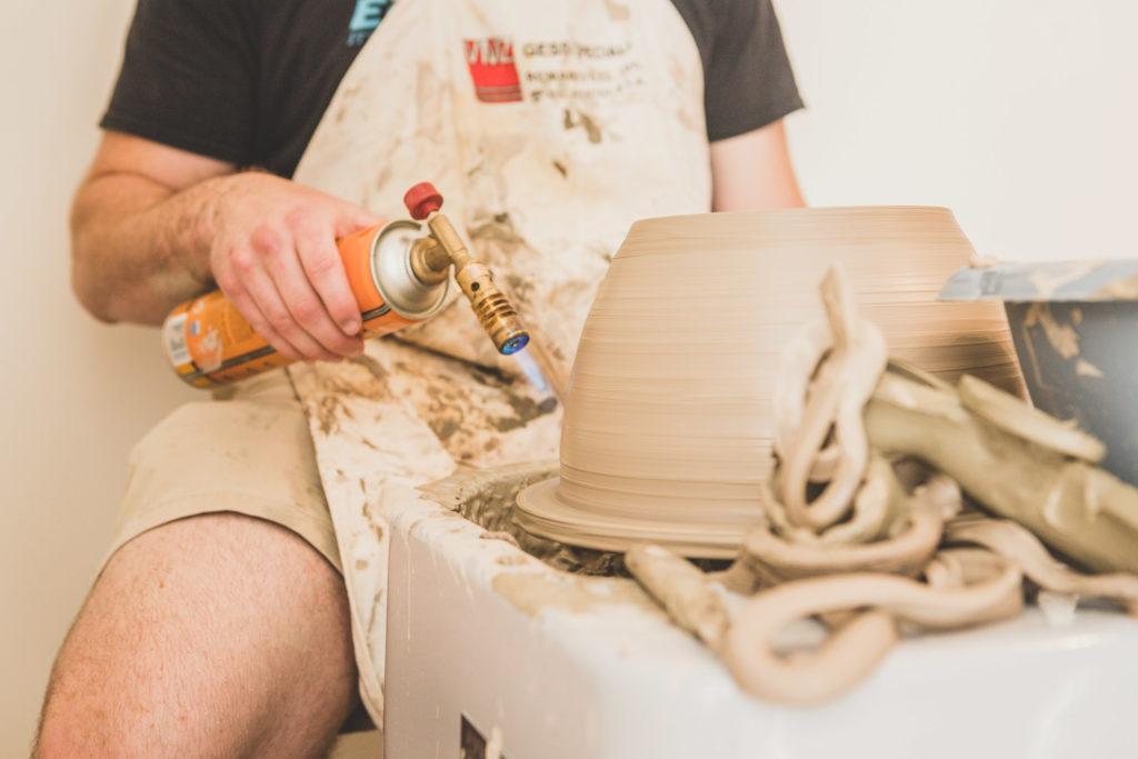 Shane Lutzk, artista americano in residenza artistica presso il museo della ceramica di Savona, lavora al al tornio per modellare parte del proprio vaso e ne rifinisce i dettagli con la fiamma ossidrica