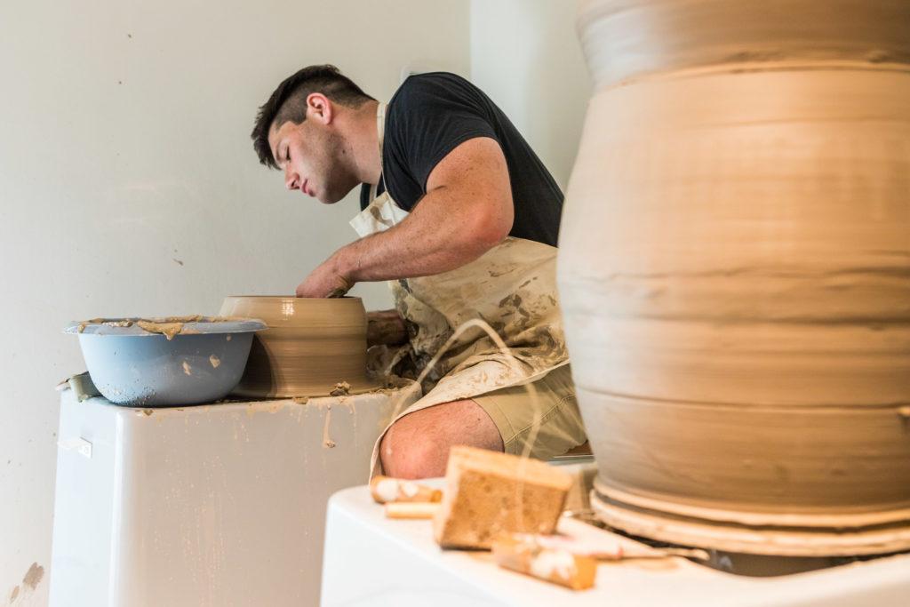 Shane Lutzk, artista americano in residenza artistica presso il museo della ceramica di Savona, lavora al al tornio per modellare parte del proprio vaso