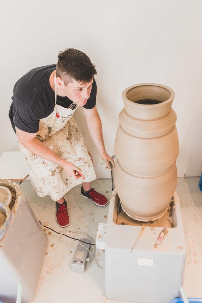 shane lutzk concentrato nel comporre uno dei suoi vasi giganti, in abiti da lavoro