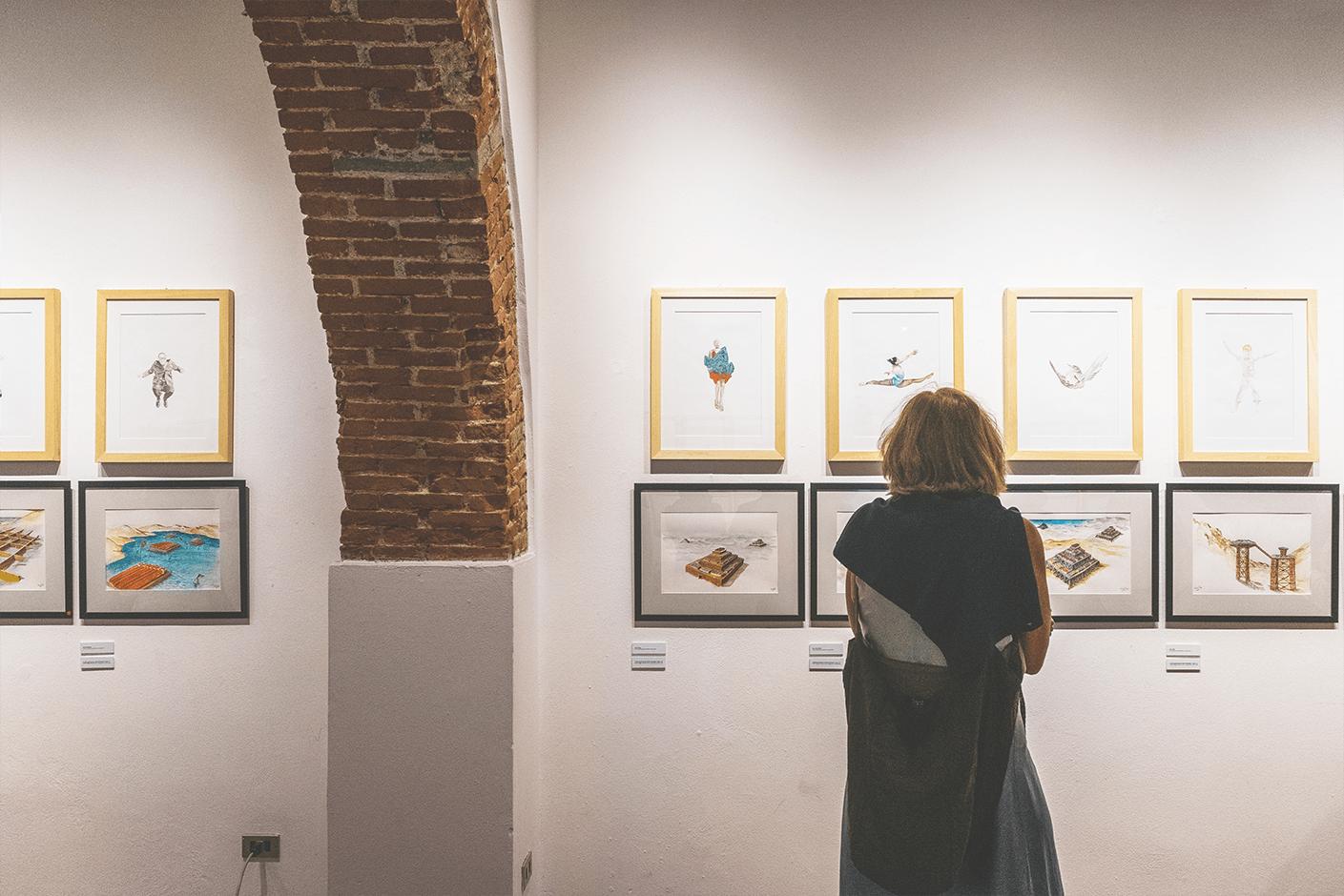 una visitatrice guarda gli acquerelli di franco raggi e lucia lamacchia