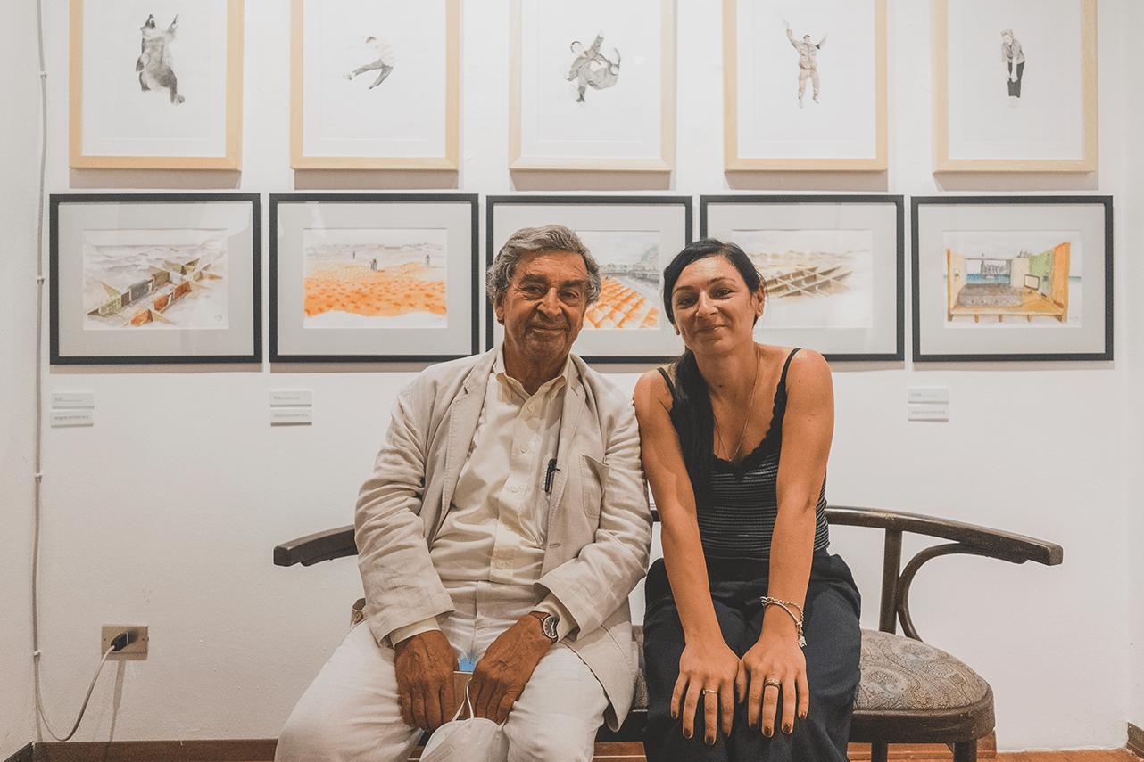 gli artisti e designer franco raggi e luci lamacchia seduti di fronte ale loro opere