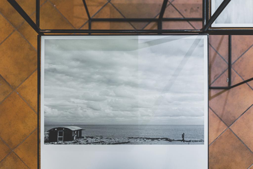 foto di marcello campora in esposizione che raffigura un piccolo capanno sul mare a sinistra, una persona che cammina a destra, un cielo pieno di nuvole