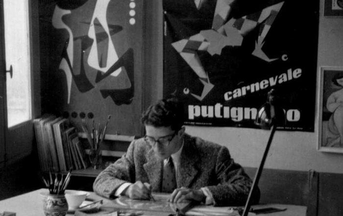 Foto storica in bianco e nero del grafico Mimmo Castellano a lavoro. Sullo sfondo si può vedere il manifesto sula Maschera Favinella